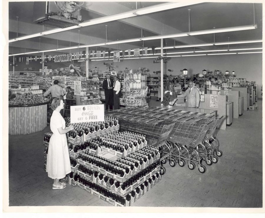 1957 Lamb's Thriftway grand opening. Forrest Lamb stands at first checkout register.