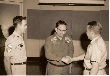 US Army Sgt. 1st Class Steele, center, shaking hands with a General