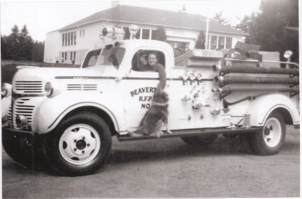 1950s Jean Johnson and dog Billy Boy at Garden Home Garage. Truck is local Volunteer Beaverton Fire Department.