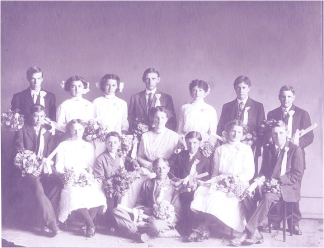 "1916 graduates with Margaret's brother, Rhinehart ""Duke"" Scherner. Teacher Miss Magnuson, L-R Back Row: Olaf Johnson, Birtha Benz, Lena Benz, Frank Erickson, Elizabeth McBroon, John Dehaan, Wesley Beharrel. Front Row: William Kehrli, Pauline West, Wilbur Workman, Adam Dehaan, Rhinehart Scherner, Ruth Caldwell, Clause Erickson."
