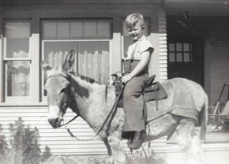 Jack Godwin on his burro, Babe, in front of Godwin home on Westgard