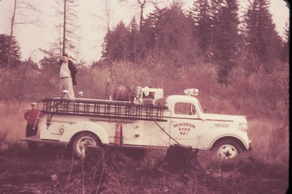 "Firefighter Clarence Buffam (on rig) and Beaverton fire chief Archie Olson use a Beaverton Rural Fire Protection District engine to fight a brush fire on King street in Garden Home area in what is now on the Oleson Road side of the Portland Golf Club. Retired firefighter Ernie Metcalfe described Olson, who was named chief of the Beaverton Fire Department in February 1937, as ""old school"" when it came to firefighting. That meant telling his firefighters to ""put the wet stuff on the red stuff."" The fire was contained by firefighters from the Beaverton Rural Fire Protection District."