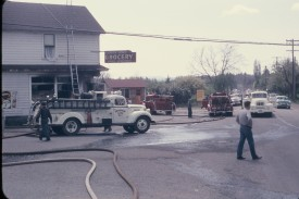 A 1953 International tanker from the Beaverton Rural Fire Protection District (foreground) helps extinguish a major fire that burned the same grocery store on the corner of Oleson and Garden Home roads in Garden Home. Aiding in the effort was the Portland Fire Bureau, their two engines visible to the right.