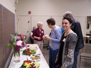 Nicole Shreve smirks while Elaine Shreve speaks with Sharon and Bob Cram, Jan Fredrickson seated - History Society Roundtable May 18, 2018