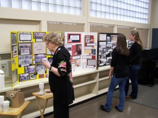 People viewing tri-fold displays - Ginny Mapes reception May 18, 2018