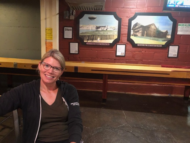 Shelly Bigley in front of the Lewis and Clark Centennial photos at the Old Market Pub